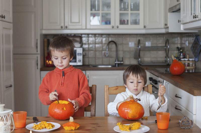 two little boys carving pumpkins at home